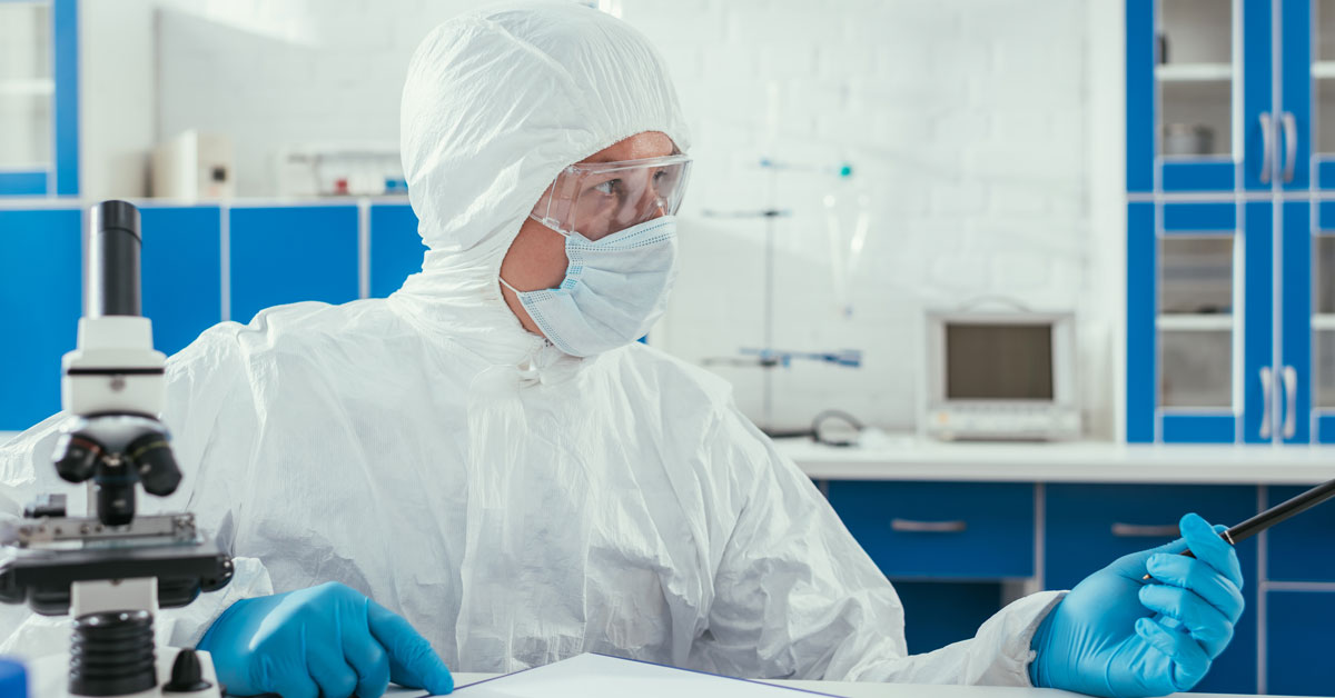 Biochemist in hazmat suit sitting near microscope