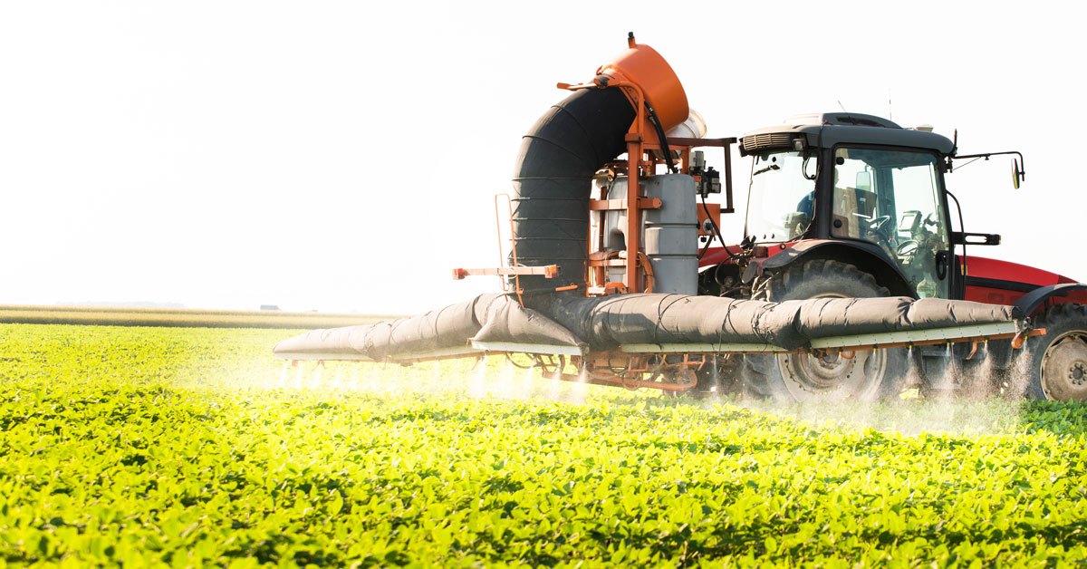 Tractor spraying glyphosate on soy field at sunset